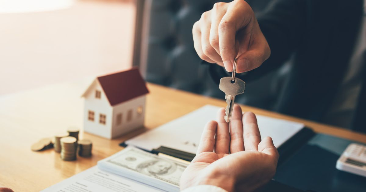 A realtor giving a first-time home buyer the key to his home